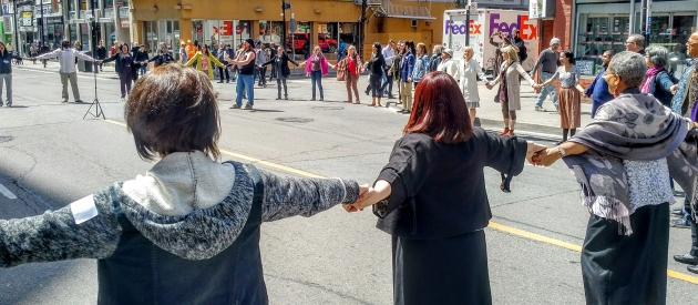 People holding hands and standing in a circle in the middle of the road